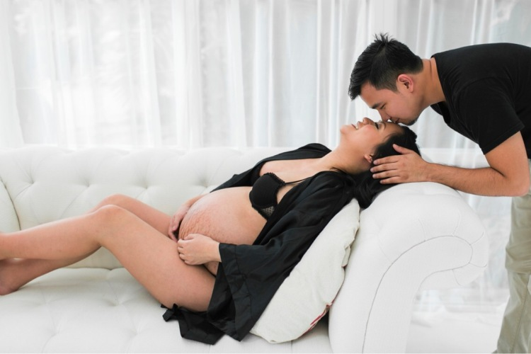 Boudoir maternity photo of woman kissed by husband