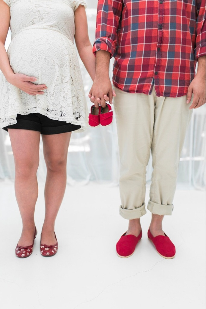 Couple holding baby shoes during maternity shoot