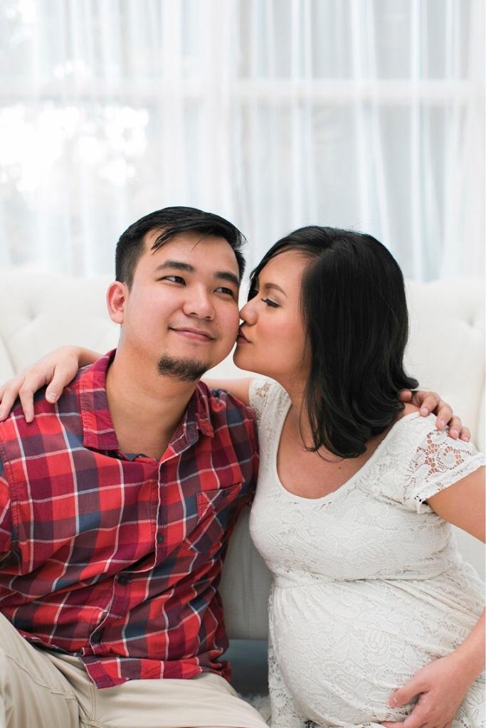 Maternity photo of woman kissing husband