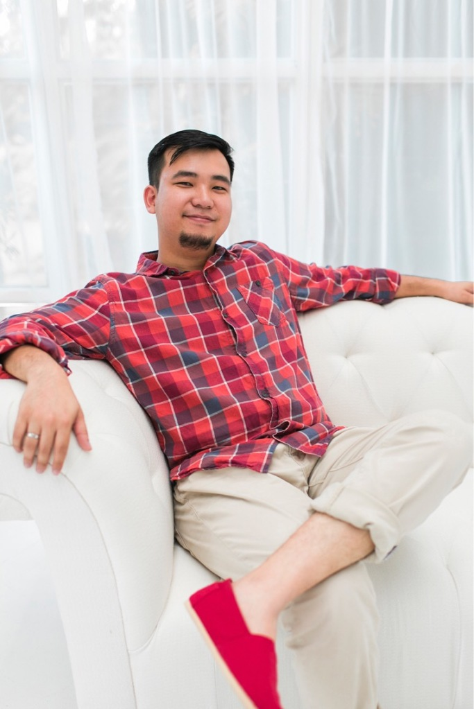 Asian man wearing Toms sits on couch