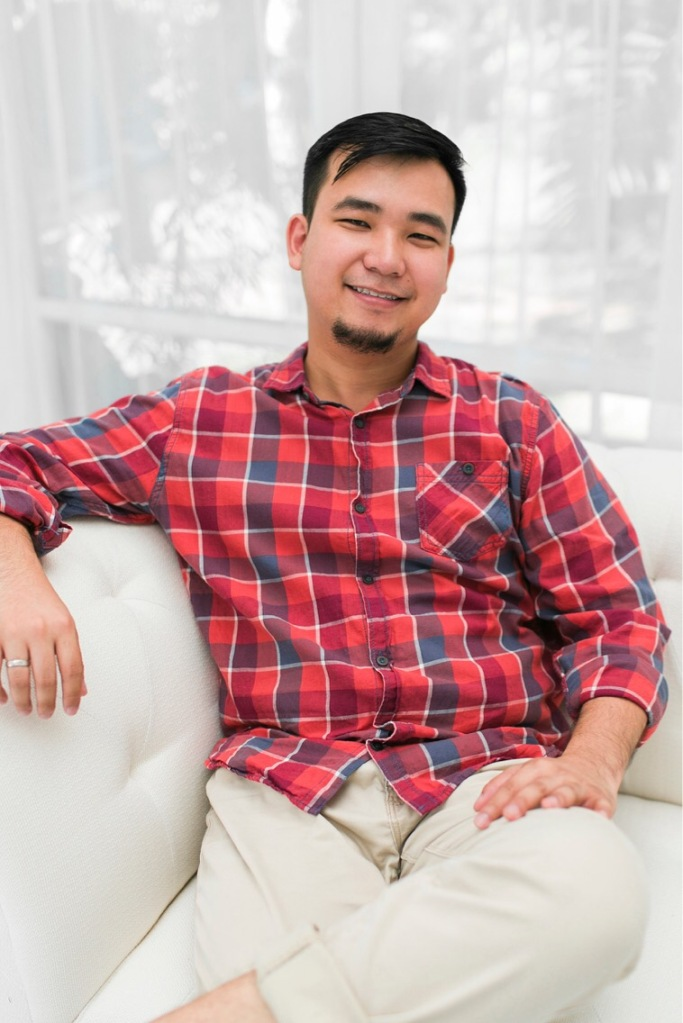 Asian man relaxes on couch