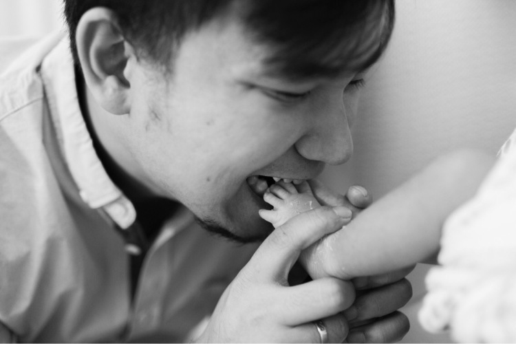 dad biting feet of newborn baby